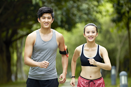 young asian man and woman couple running jogging in a city park.
