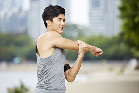 young asian man warming up by stretching arms before exercise. Banco de Imagens