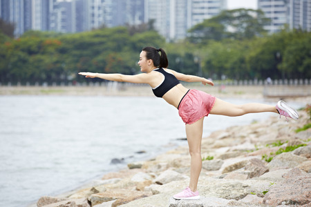 health conscious: young asian woman doing balancing exercise by lake in city park.