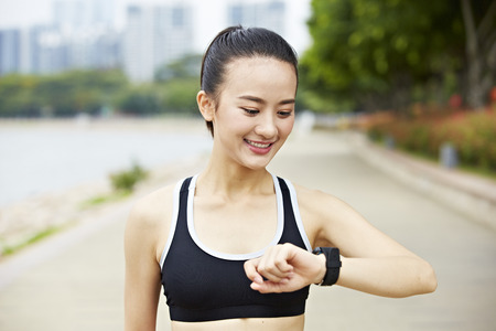 girl sport: young asian woman runner looking at fitness watch.