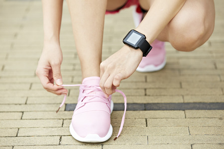 young woman runner with wearable fitness device tying shoelace, close-up.