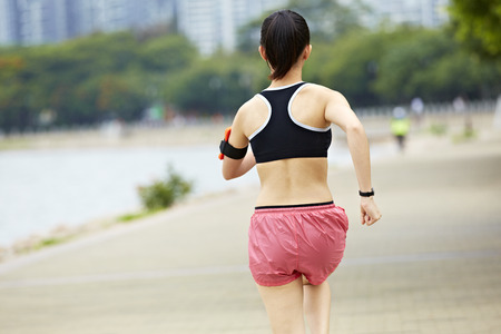 health conscious: young asian woman jogger running in a city park, rear view. Stock Photo