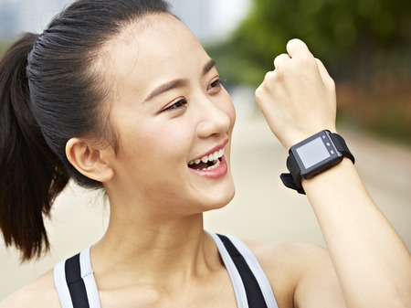answering: young asian woman jogger answering or making a call using a wrist watch wearable device. Stock Photo