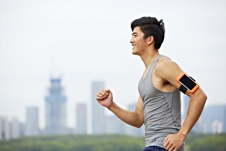 giovane jogger maschio asiatico con l'inseguitore di idoneità attaccato al braccio in esecuzione con skyline in background.