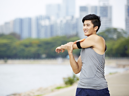 health conscious: young asian male jogger with fitness tracker attached to arm warming up by stretching arms and upper body before running, city skyline in the background.