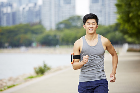 joyous: young handsome asian jogger running exercising in city park wearing fitness tracker