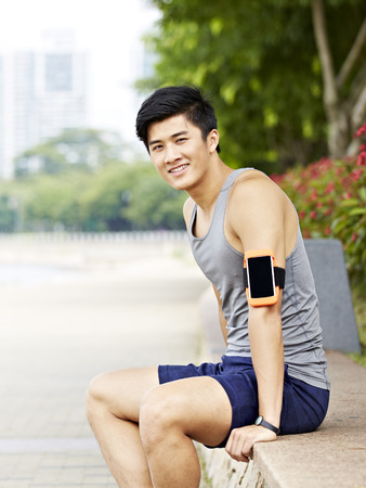 hombres jovenes: young handsome asian jogger wearing fitness tracker taking a break in a city park, looking at camera with a big smile