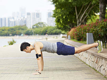 asian lifestyle: asian young man doing exercising by doing push-ups in a city park Stock Photo