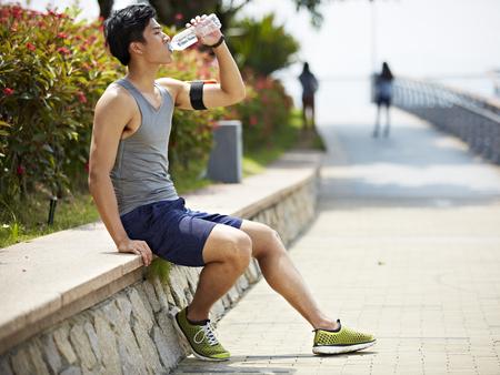 jovem e bonito corredor asiático que toma uma ruptura e beber água de uma garrafa, vista lateral