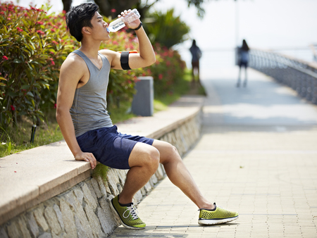 replenishing: young handsome asian jogger taking a break and drinking water from a bottle, side view