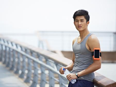 Junge gut aussehend asiatischen Rüttlereignung tracker trägt eine Pause eine Flasche Wasser in die Kamera Standard-Bild