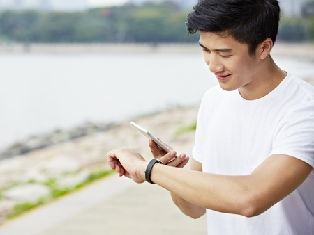 young asian man using apps in smartphone and smartwatch to track fitness data during exercise Stock Photo