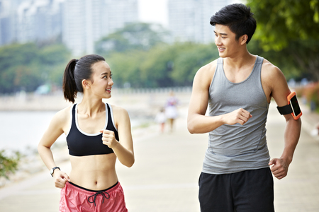 young asian man and woman couple jogging in a park, talking and looking at each other