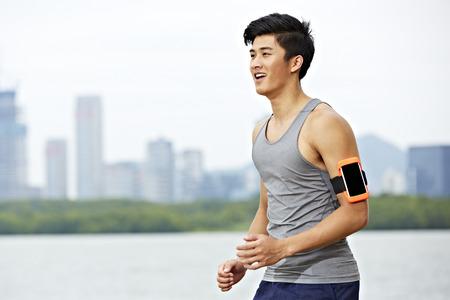 puls: Young Asian mężczyzna jogging z trackerem siłowni załączonym uzbroić działa z skyline w tle.
