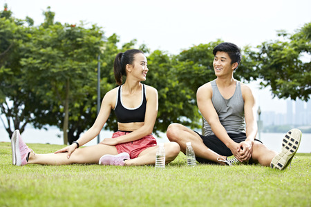 singaporean: young asian couple or friends talking to each other while stretching legs on grass