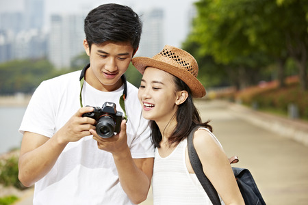 若いアジアのカップルの観光客が撮影した画像を確認するカメラのモニターを見て