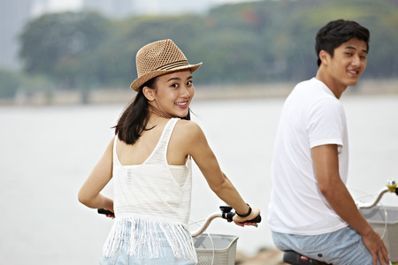 young asian couple turning to camera smiling while riding bicycle outdoors, slightly grainy