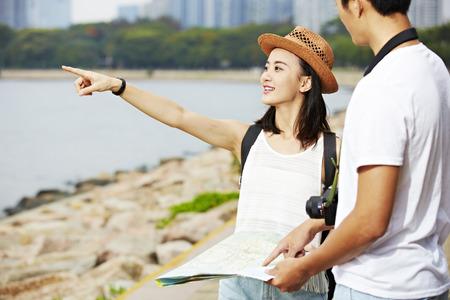 若いアジアのカップル観光客マップを使用して風景スポットを検索しよう 写真素材