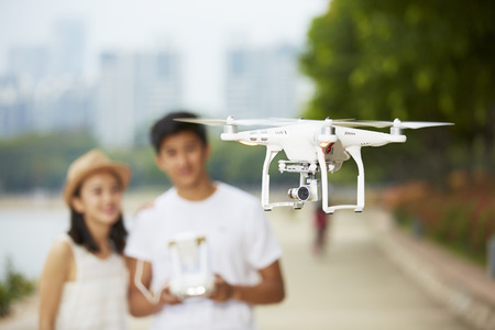 a hobby: young asian couple operating a drone in a city park, selective focus on the drone