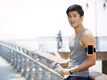young asian man taking a break with a bottle of water in hands during outdoor exercise