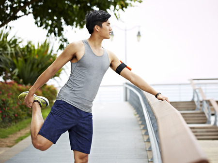 korean man: young asian athletic man warming up before running by stretching a leg