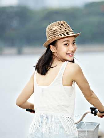 young and beautiful asian girl turning to camera smiling while riding bicycle