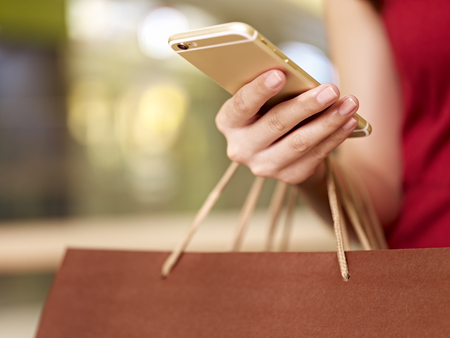 hand of a young woman carrying shopping bags using mobile phone