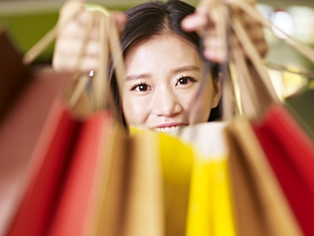 joyous: young asian woman showing what she has bought during a shopping spree