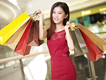 joyous festivals: young asian woman carrying paper bags walking in mall, happy and smiling