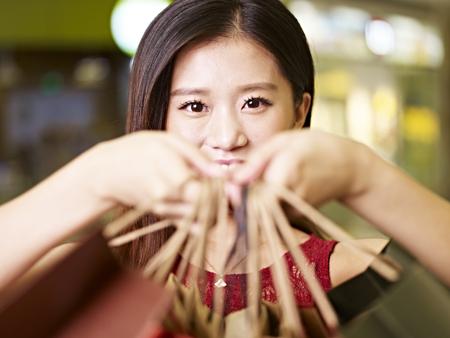 shopping trip: young asian woman showing what she has bought during a shopping trip
