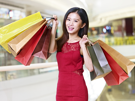 young asian woman on shopping spree carrying paper bags walking in mall, happy and smiling