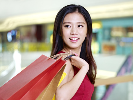 shopping spree: young asian woman on shopping spree carrying paper bags walking in mall, happy and smiling