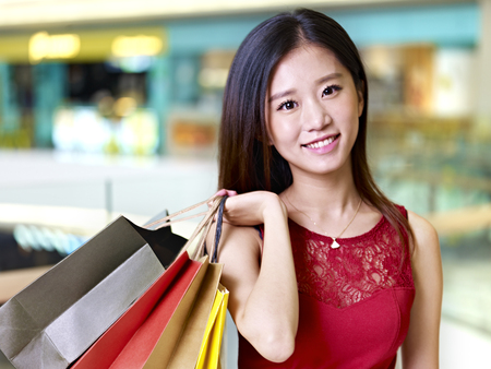 shoulder carrying: young asian woman on shopping spree carrying paper bags on shoulder walking in mall, happy and smiling
