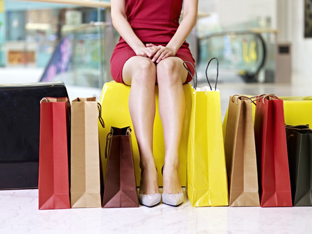 shopper: young female woman shopper with beautiful legs surrounded by colorful shopping bags resting in mall or department store Stock Photo