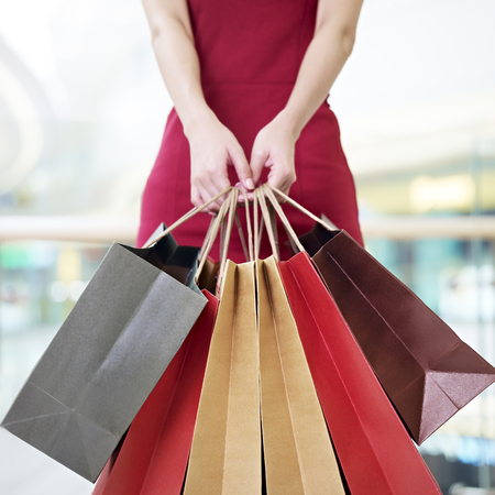 shopping mall: young woman female shopper standing with colorful paper bags in hands in shopping mall or department store, focus on paper bags