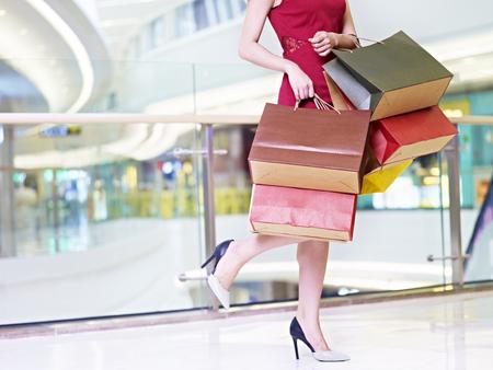 jonge trendy en modieuze vrouw vrouwelijke shopper uitvoeren kleurrijke papieren zakken lopen in het moderne winkelcentrum