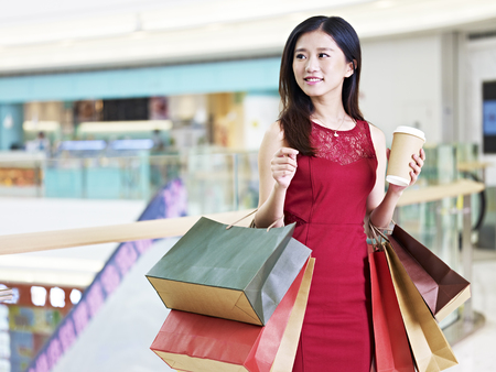 young beautiful asian woman female shopper carrying colorful paper bags and a cup of coffee walking in shopping mall Standard-Bild