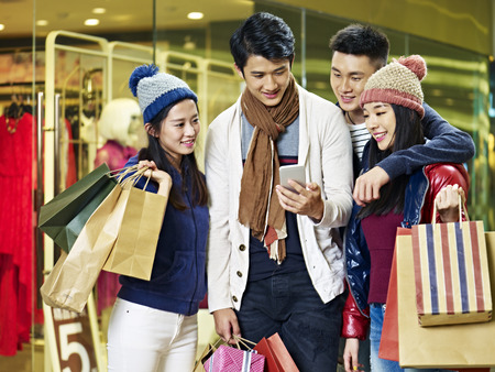having fun in winter time: two asian couples using cellphone and sharing information while shopping for christmas in mall or department store Stock Photo