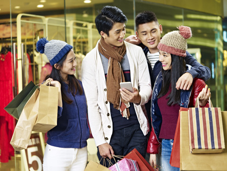 two asian couples using cellphone and sharing information while shopping for christmas in mall or department store Stock Photo