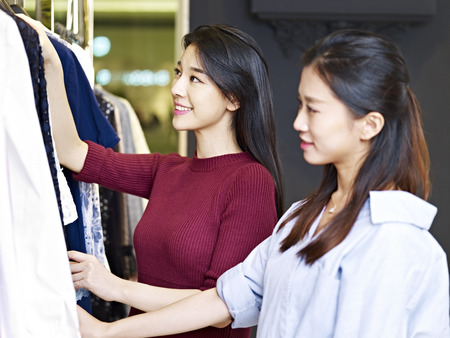 beautiful young asian women looking at apparels in a clothing store