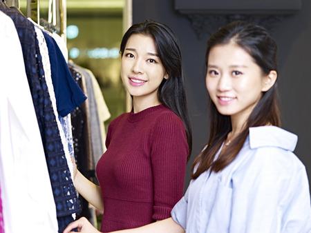 アパレル衣料品店の前に笑みを浮かべてカメラを見て美しい若いアジア女性