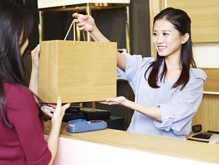 Joven vendedor asiático femenino entregando una bolsa de papel de mercancías a un cliente en el mostrador de salida