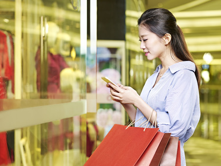 jonge Aziatische vrouw die met behulp van mobiele telefoon tijdens het winkelen in winkelcentrum of warenhuis