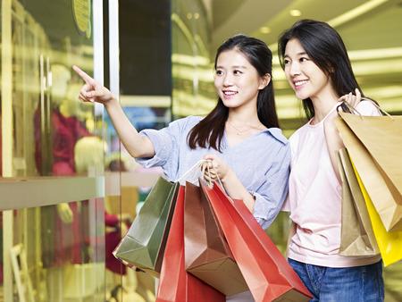 window shopper: two beautiful young asian woman shopping in mall or department store