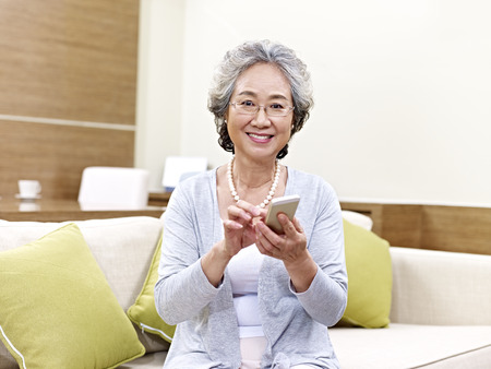 senior asian woman looking at camera smiling while using mobile phone at home