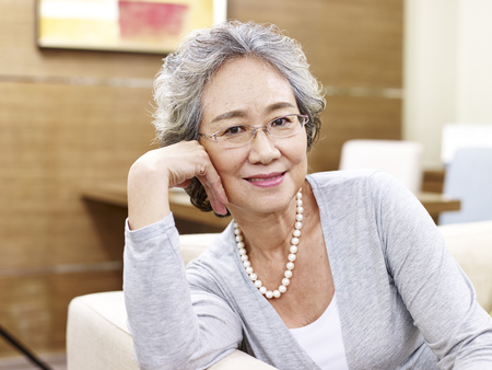 señora mayor: portrait of a senior asian woman, sitting on couch looking at camera smiling