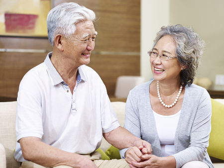 70s: happy senior asian couple sitting on couch talking at home, smiling, holding hands Stock Photo