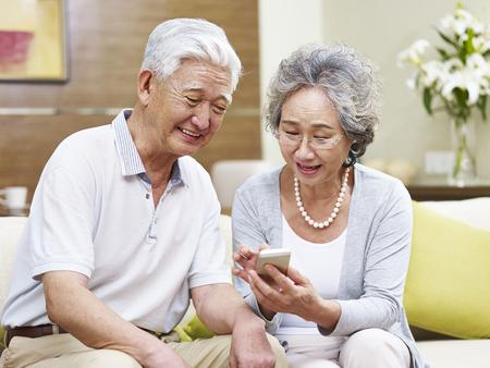 Gelukkig senior Aziatisch paar kijken naar mobiele telefoon thuis, blij en lachend Stockfoto