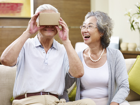 senior asian couple amazed by the technology while trying vr glasses Imagens