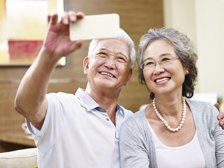 senior asian couple taking a selfie at home using cellphone